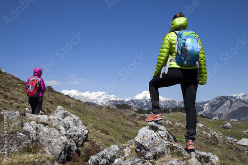 Hikers walking on hike in mountain nature landscape in Slovenian Alps. Hiking – sporty hiker woman on trek with backpack living healthy active lifestyle