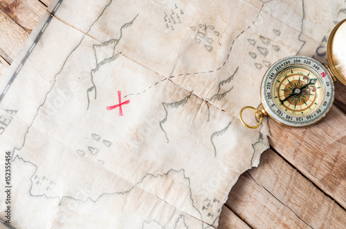 Top view to vintage fake treasure map with red cross and compass on wooden desk