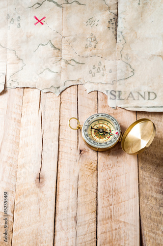Compass on wood table with fake abstract Treasure map