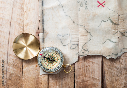 Compass on wooden desk with fake pirates treasure old map with red mark cross