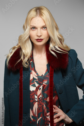 Beautiful fashion model in dress with print and coat with fur collar Poster