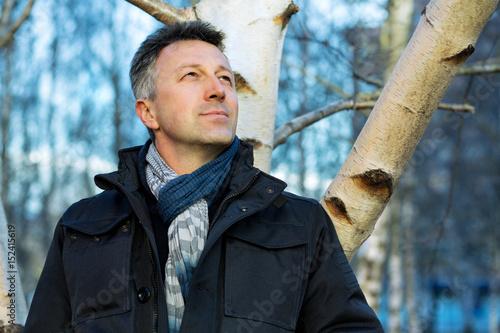 Papiers peints Bosquet de bouleaux Handsome happy smiling man. Outdoor autumn male portrait. Attractive confident middle-aged man posing in city park, birch grove.
