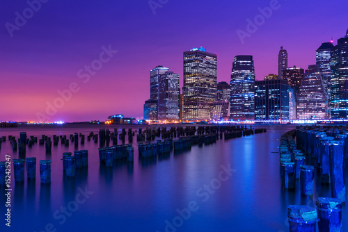 New York city skyline at night, Manhattan skyscrapers reflected in water, NY, USA