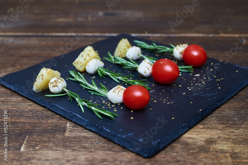 Skewers made of rosemary with cheese and tomatoes