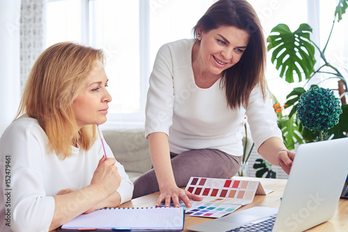 Pleased madams working with catalog of color palette and laptop