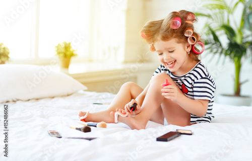 Papiers peints Pedicure Happy funny child girl with hair curlers does a pedicure, paints nails and laughs