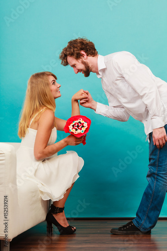 Man giving woman candy bunch flowers. Happy couple Poster