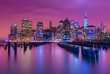 Manhattan skyline at night with varicolored reflections in the water, view from Brooklyn, New York, USA