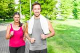 Portrait of cheerful caucasian couple running in the park