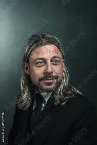 Smiling retro victorian style man with blond long hair and beard. Wearing black suit and tie.