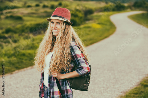 Beautiful young woman enjoys at the country road.