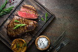 Grilled beef steak on wooden board. Top view copy space.