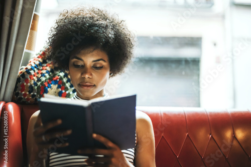 Young concentrated woman reading book