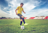 Asian boy teenager playing football at the stadium, sports, outdoor activities