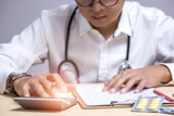 Doctor with stethoscope calculate paper sheet and writing prescription on office desk hospital