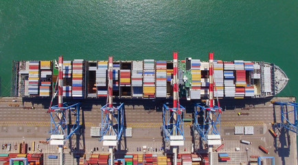 Commercial port with container ship during loading and unloading - Top down view.