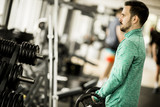Handsome young man uses dumbbells in gym
