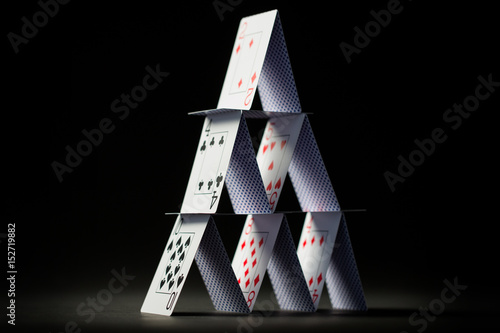 house of playing cards over black background плакат
