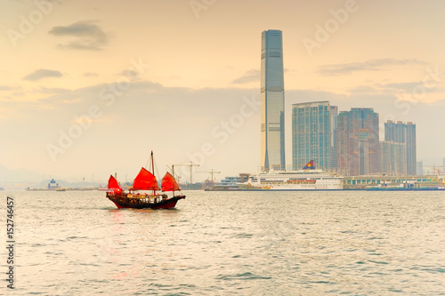 Hong Kong skyline with a red Chinese sailboat passing on the Victoria Harbor at Poster
