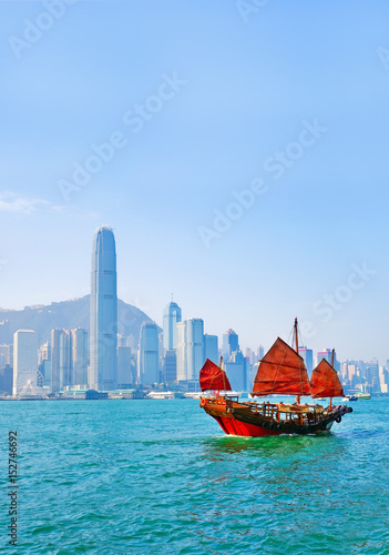 View of Hong Kong skyline with a red Chinese sailboat passing on the Victoria Harbor in a sunny day Poster