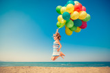 Happy child jumping with colorful balloons on sandy beach - 152816265