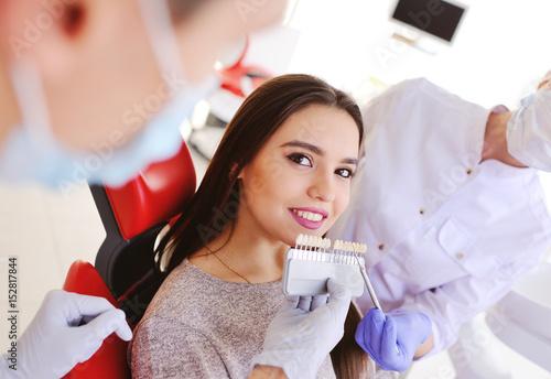 Dentysta wybiera odcień szkliwa zęba za pomocą specjalnej skali stołu