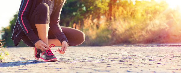 Runner Woman Tying Her Shoelaces While Jogging - Sport And Fitness At Sunset