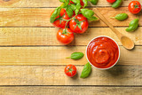 Delicious ketchup with basil and tomatoes on wooden background, top view