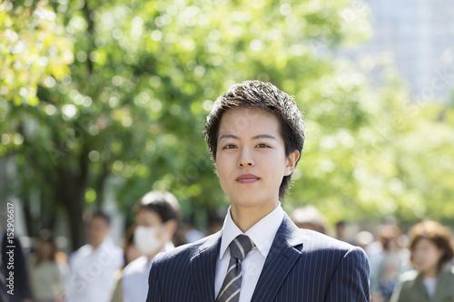 通勤するビジネスマン 朝 東京駅前 通勤の人々背景 カメラ目線 笑み