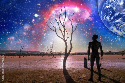 Foto op Plexiglas Draken Fantasy landscape of the future - Person silhouette standing on barren land with bare trees and huge planet rising, galaxy in the sky. Elements of this image are furnished by NASA