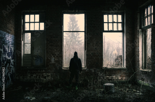 Fotobehang Oude verlaten gebouwen Lonely depressed man standing at dark abandoned factory.