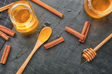 Cinnamon and honey in jars on table, top view