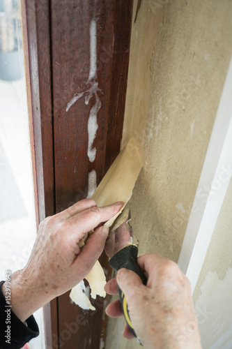 Frau kratzt mit einem Spachtel alte Tapete von der Wand