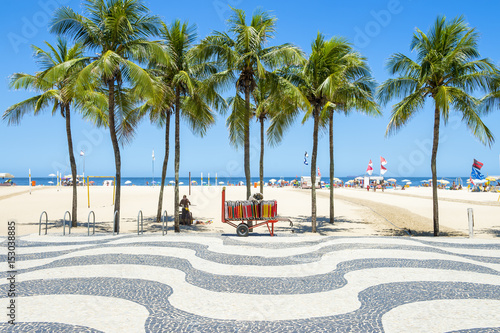 Plakat Bright scenic view of Copacabana Beach with palm trees beside the iconic boardwa