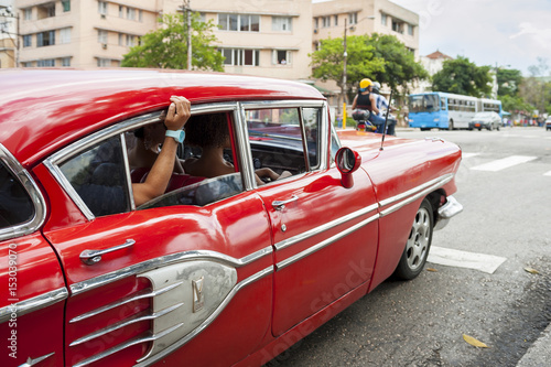Vintage American car serving as shared taxi driving along a street in Central Havana, Cuba