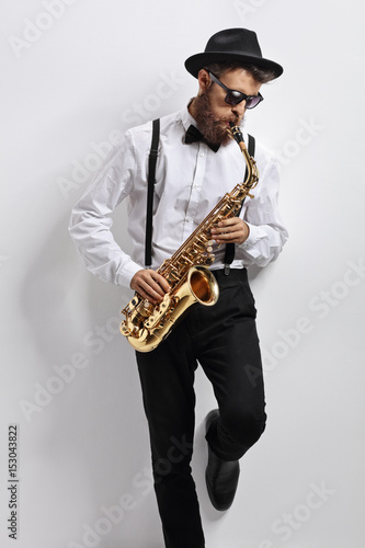 Jazz musician leaning against a wall and playing saxophone Poster
