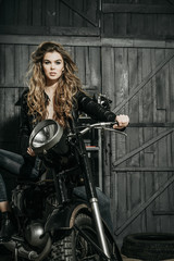 Sexy pretty biker in leather jacket sitting on vintage motorcycle