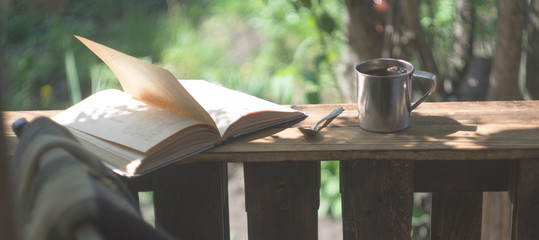 Metal mug, book and chair on a wooden terrace © natagolubnycha