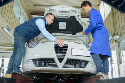 Men working on car on production line