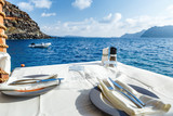 Served table with white tablecloth against blue water of Aegean sea on Santorini island resort in Greece, Europe. - 153212218