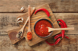 Composition with tasty chili sauce on wooden table