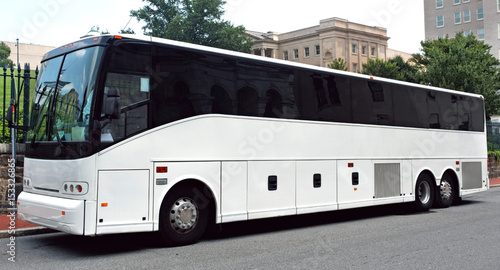 Parked white tour charter bus with dark tinted windows.