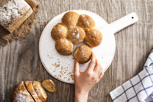 Female hand breaking freshly baked bread Poster