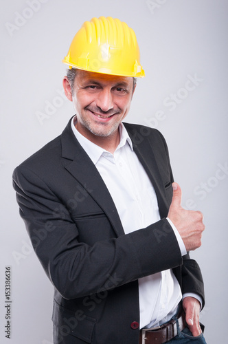 Foreman wearing hardhat making thumb up gesture