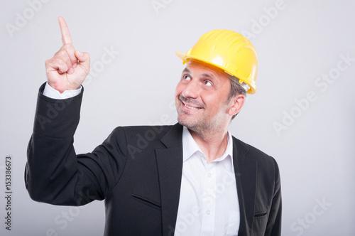 Foreman wearing hardhat pointing up