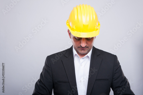 Contractor wearing hardhat arranging jacket