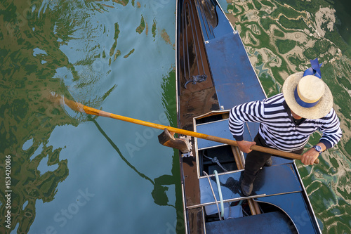 Abstract view from above of a traditional Venetian gondola passing along the green waters of a canal in Venice, Italy