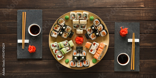 Set of sushi maki and rolls on black rustic wood, top view Poster