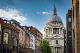 St Paul cathedral seen from a narrow alley enclosed by brick buildings on a cloudy summer day in London, England,UK. St Paul's is an important landmark of London