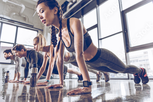 Poster group of athletic young people in sportswear doing push ups or plank at the gym, group fitness concept